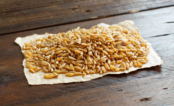 Pile of Kamut grain on wooden background - Stock Photo - Images