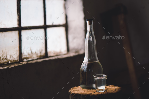Strong alcohol drink in bottle with shot glass - Stock Photo - Images