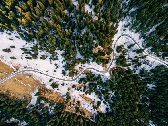 Aerial view of snowy forest with a road. Captured from above with a drone - Stock Photo - Images