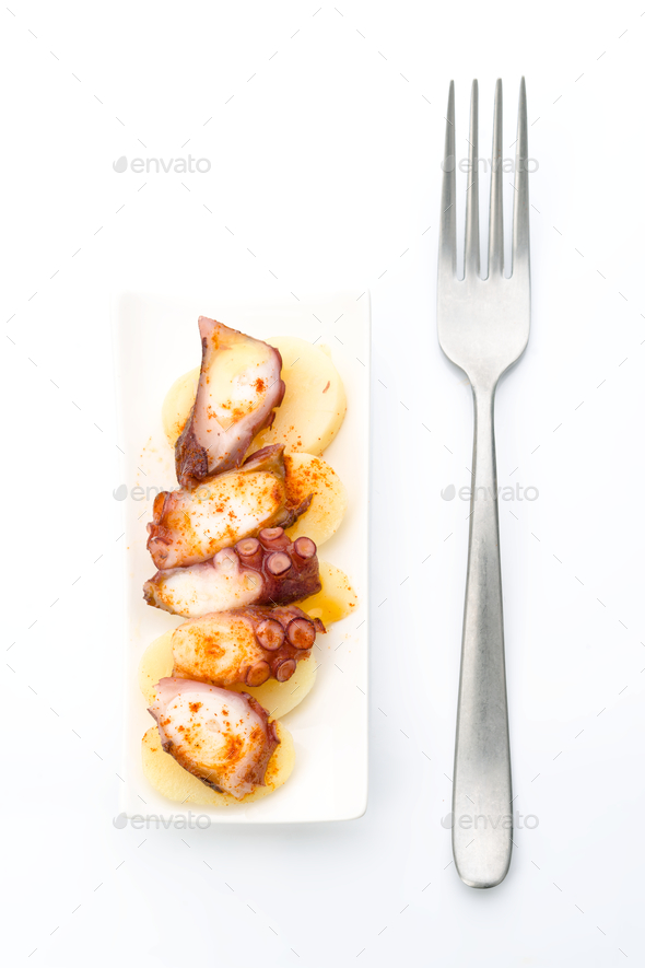 Marinated octopus sliced on potatoes isolated on white - Stock Photo - Images