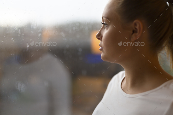 Thoughtful woman looking out the window - Stock Photo - Images