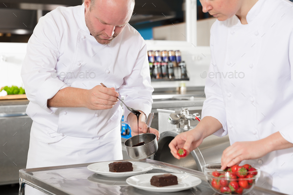 Professional chefs decorate dessert cake with lemon leaf - Stock Photo - Images