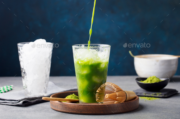 Matcha, green tea ice tea in tall glass on wooden plate. Grey stone background. - Stock Photo - Images