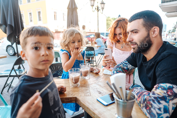 family in a cafe, mom takes a photo - Stock Photo - Images