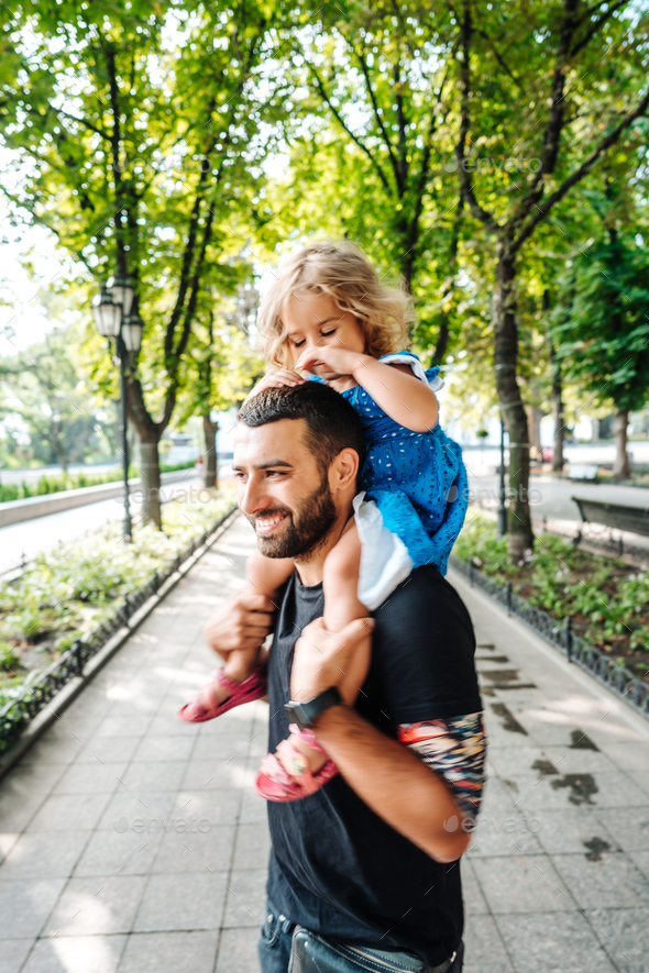 little girl riding on dads neck - Stock Photo - Images