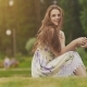 Young Beautiful Woman in Summer Dress with Long Hair Sitting on Grass in Green Park and Talking on - VideoHive Item for Sale