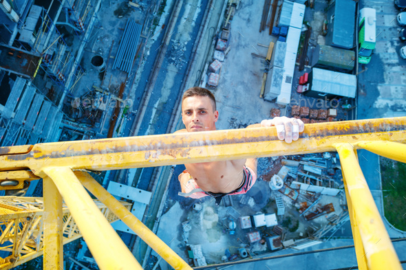 Rock climber hanging on jib of construction crane with one hand - Stock Photo - Images