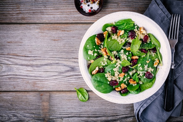 Green salad bowl with spinach, quinoa, walnuts and dried cranberries - Stock Photo - Images