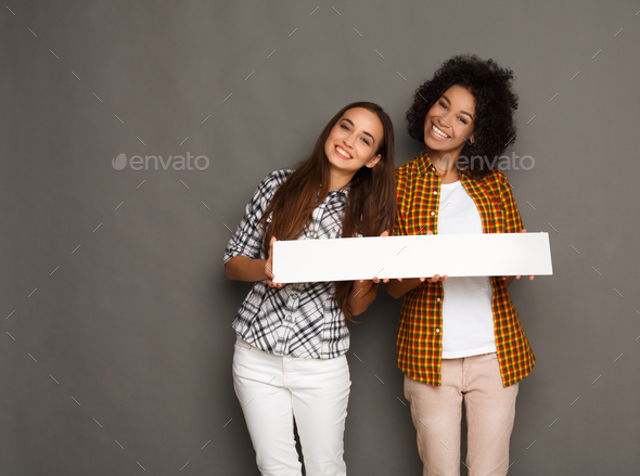 Two girlfriends holding blank white banner - Stock Photo - Images