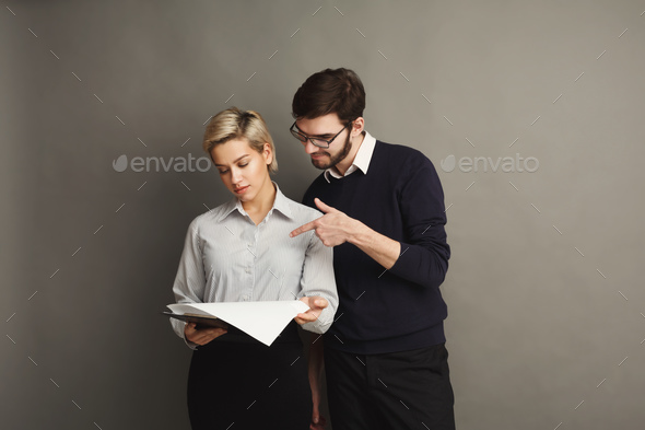 Serious couple in formal clothes on gray background - Stock Photo - Images