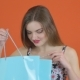 Girl Shopper Looks in Shopping Bag on Orange Background in Studio - VideoHive Item for Sale