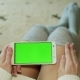 A Woman Sits on the Floor and Holds a Smartphone with a Green Display - VideoHive Item for Sale
