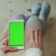 A Sexy Woman Sits on the Floor and Holds a Smartphone with a Green Screen for Your Content - VideoHive Item for Sale