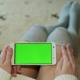 A Woman Is Sitting on the Floor and Holding a Smartphone with a Green Screen - VideoHive Item for Sale