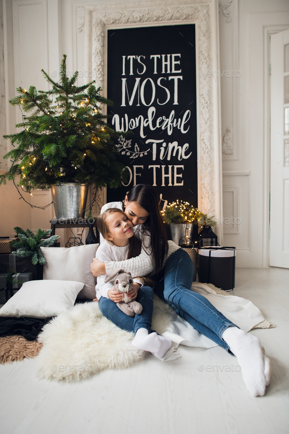 Close-up photo of little girl in knitted sweater kiss her mother while sitting on sofa at Christmas - Stock Photo - Images