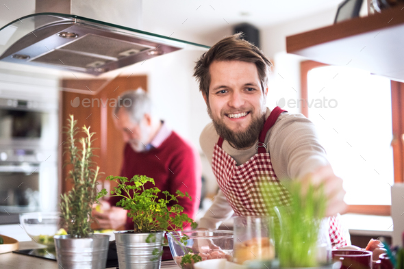 Hipster son with his senior father cooking in the kitchen. - Stock Photo - Images