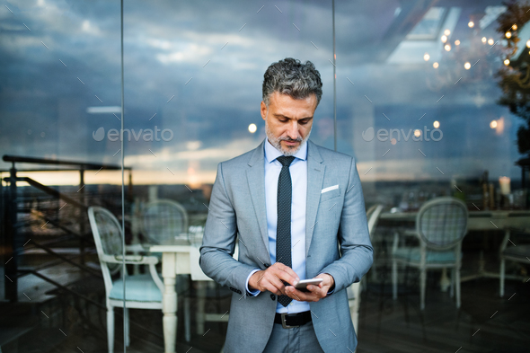 Businessman with smartphone in an outdoor hotel cafe. - Stock Photo - Images