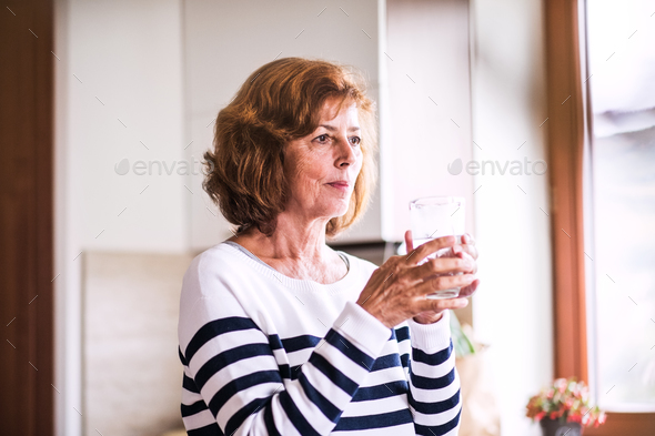 Senior woman holding a glass of water in the kitchen. - Stock Photo - Images
