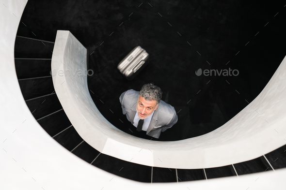 Businessman with suitcase standing at staircase. - Stock Photo - Images