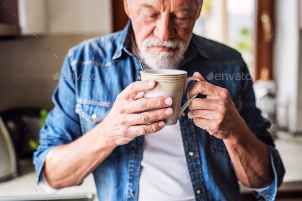 Senior man holding a cup of coffee in the kitchen. - Stock Photo - Images