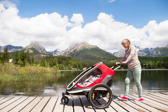 Senior woman and children in jogging stroller, summer day. - Stock Photo - Images