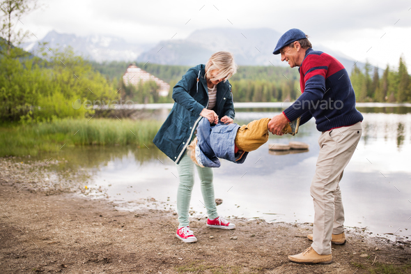 Senior couple with little boy at the lake. - Stock Photo - Images