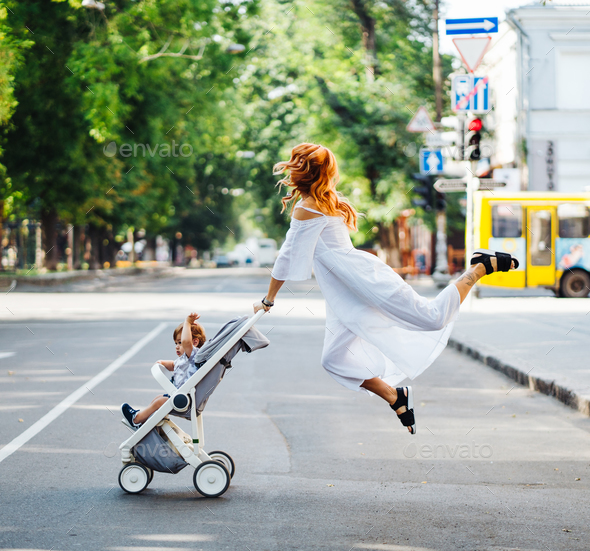 mom with a stroller crosses the road - Stock Photo - Images