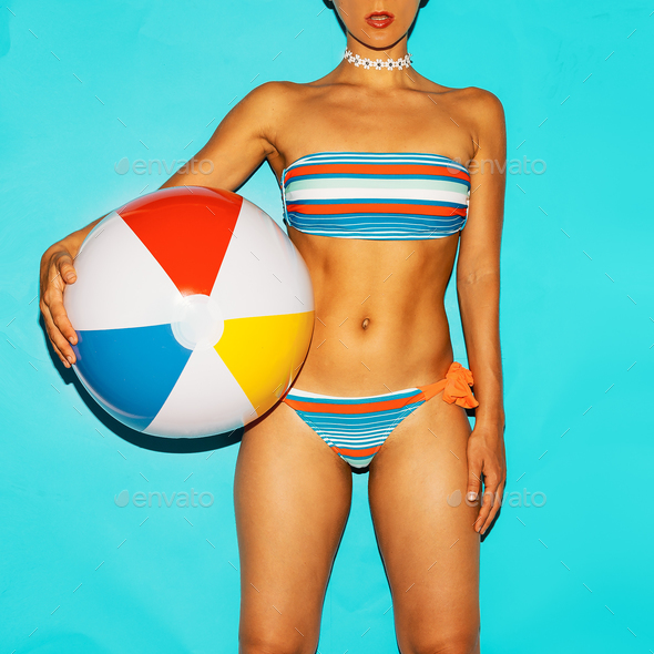 Girl in fashionable swimsuit and beach ball. Summer trend - Stock Photo - Images