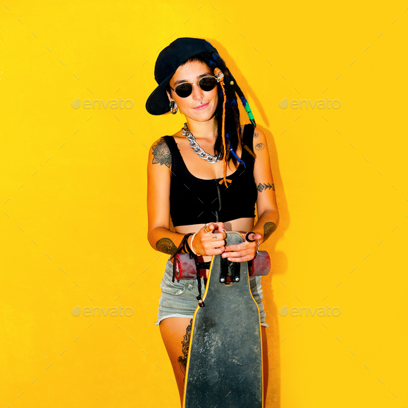 Fashion teenager girl with dreadlocks and tattoos. Skateboard  s - Stock Photo - Images