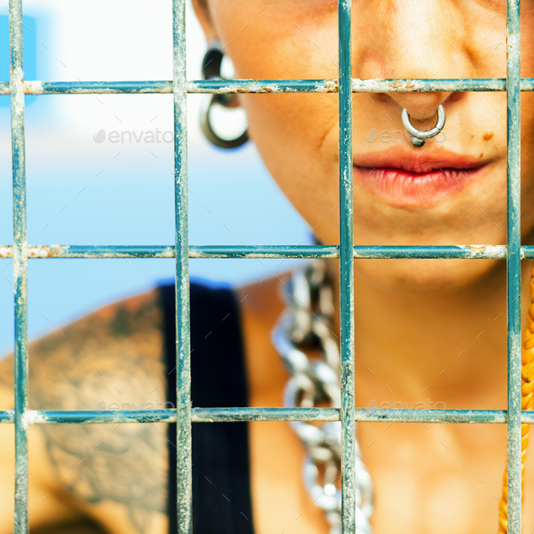 Teen behind the metal grid on sports ground - Stock Photo - Images