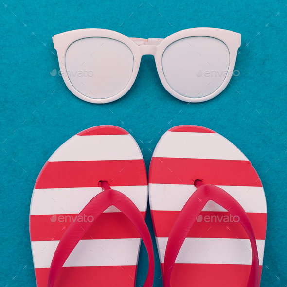 Fashion beach accessories. Sunglasses and flip-flops. Minimal de - Stock Photo - Images