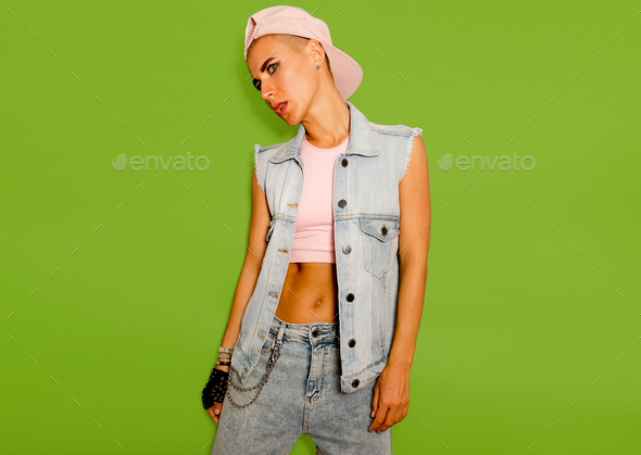 Tomboy model in denim style outfit on a green background - Stock Photo - Images