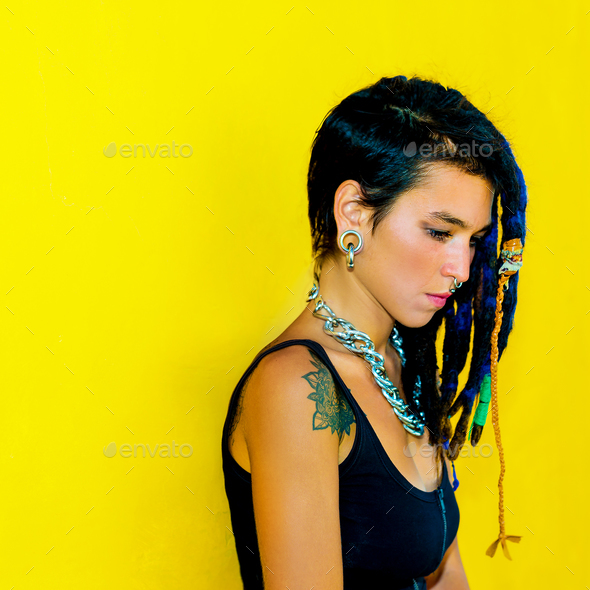 Cool Colombia girl with dreadlocks and piercings over colorful y - Stock Photo - Images