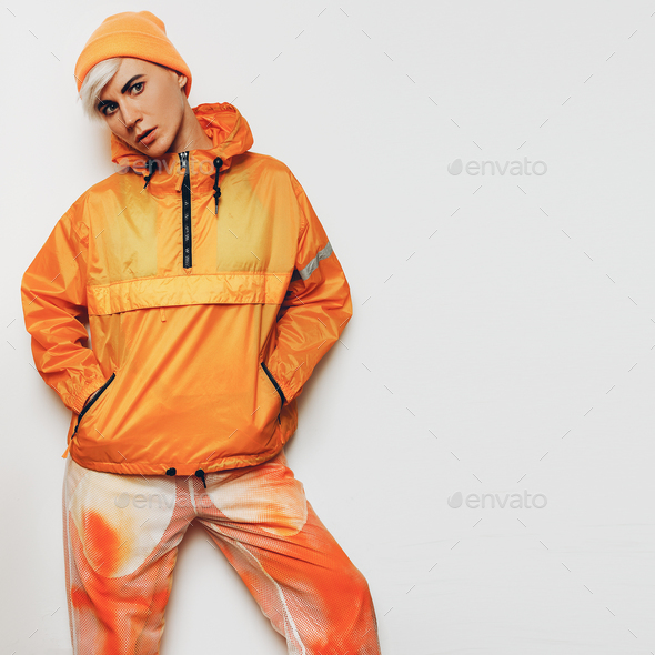 Trendy Urban Outfit Tomboy girl in a bright orange sports clothi - Stock Photo - Images