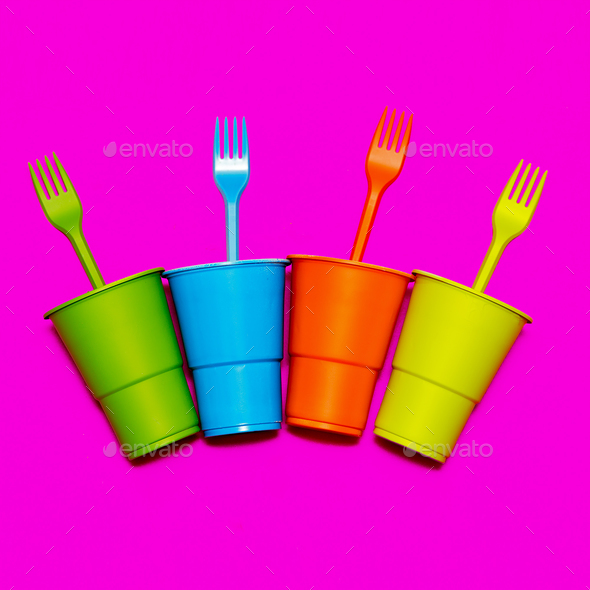Plastic tableware. Minimal. Multicolored glasses and forks - Stock Photo - Images