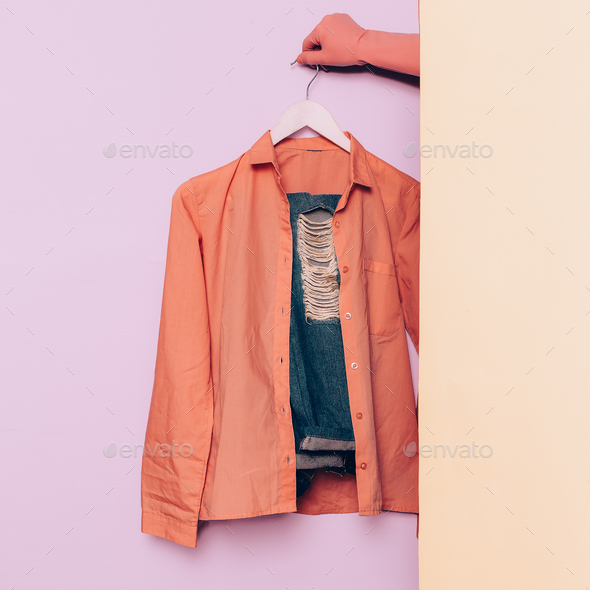 Stylish clothes. Hipster fashion. Pink shirt and jeans on a hang - Stock Photo - Images