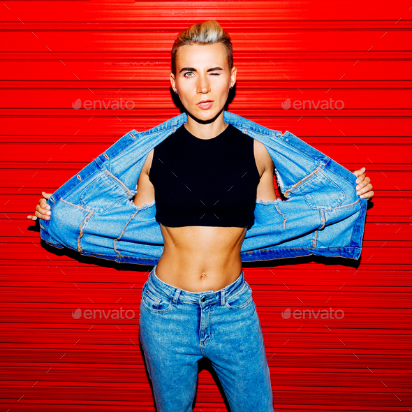 Stylish model in jeans outfit on a red background. Street style - Stock Photo - Images