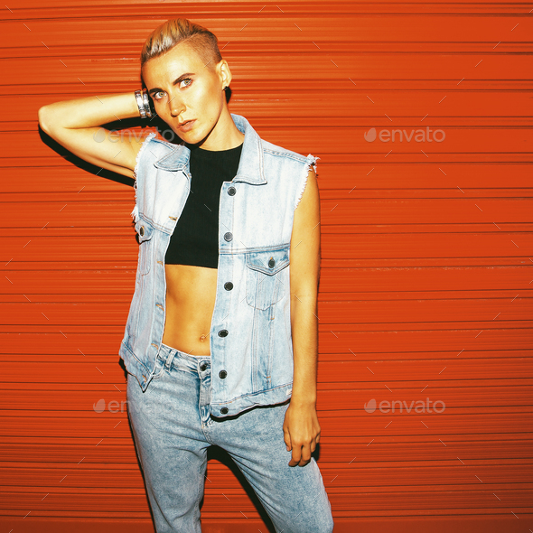 Stylish Tom boy model in jeans outfit on a red background. Stree - Stock Photo - Images