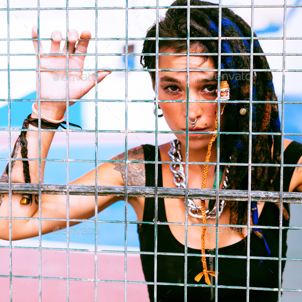 Girl with dreadlocks behind the metal grid on sports ground - Stock Photo - Images