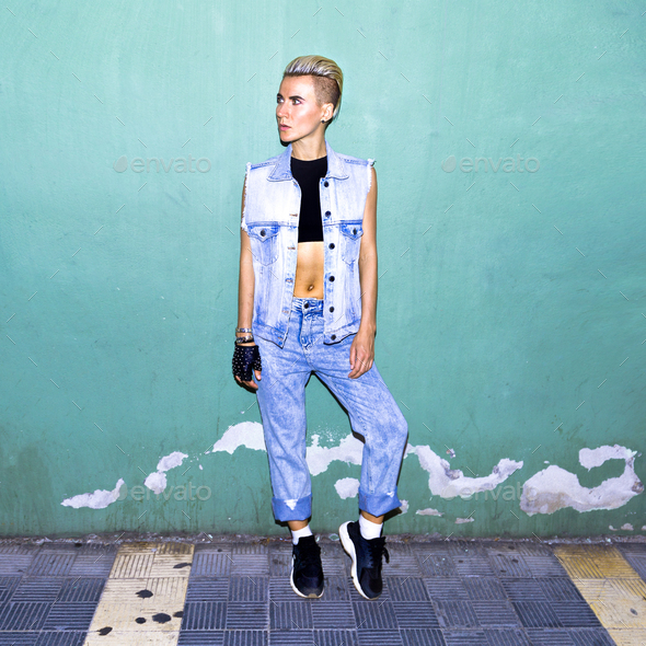Model in a stylish jeans outfit near a blue wall - Stock Photo - Images