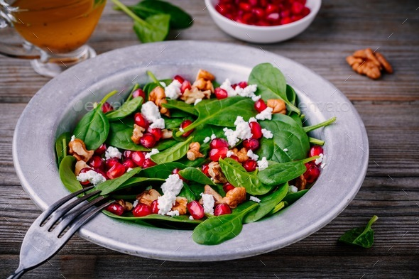 Fresh green salad with spinach, walnuts, goat cheese and pomegranate - Stock Photo - Images