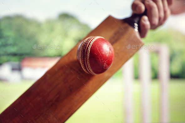 Cricket player hitting ball - Stock Photo - Images