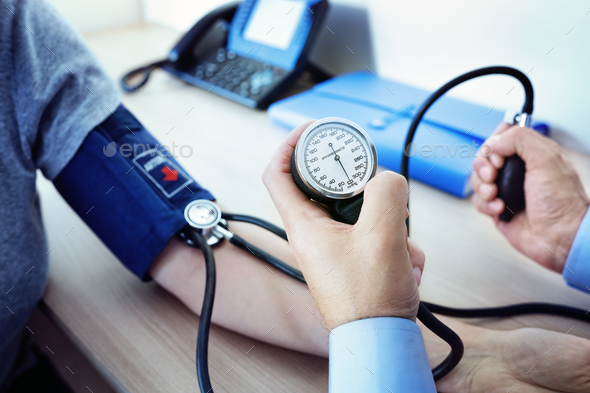 Doctor measuring blood pressure of patient - Stock Photo - Images