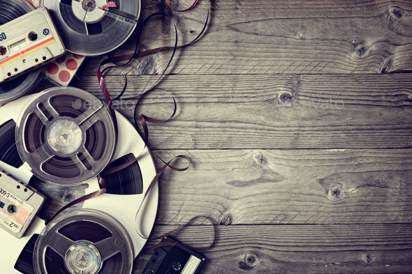 Old audio reels and cassette tape background - Stock Photo - Images