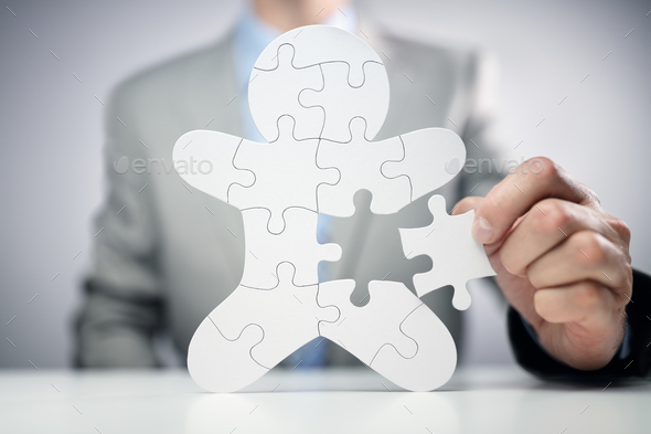 Businessman assembling jigsaw puzzle human team employee - Stock Photo - Images