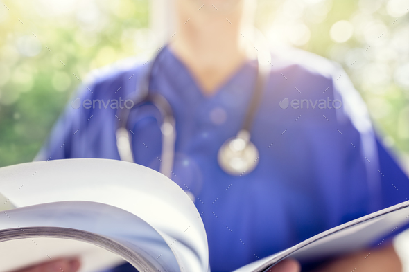 Doctor reading patient notes or medical chart - Stock Photo - Images