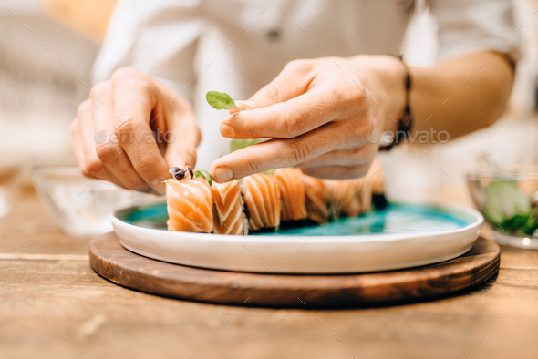 Male person cooking sushi rolls with salmon - Stock Photo - Images