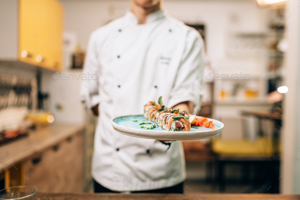 Male chef hold sushi rolls on plate, asian food - Stock Photo - Images