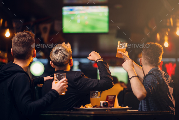 Three men watches football on TV in a sport bar - Stock Photo - Images