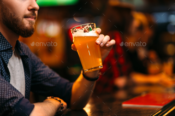 Man drinks beer at the bar counter in a sport pub - Stock Photo - Images